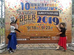 九州オータムフェスティバル看板前ではーとふるメンバー2人