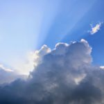 太陽が雲に隠れていて雲の切れ間から光が漏れ光線が放射状に地上へ降り注いで見える