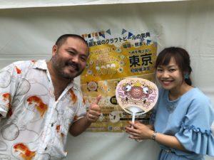 九州オータムフェスティバル2018でフライヤーの前で内輪を手にする平野綾菜