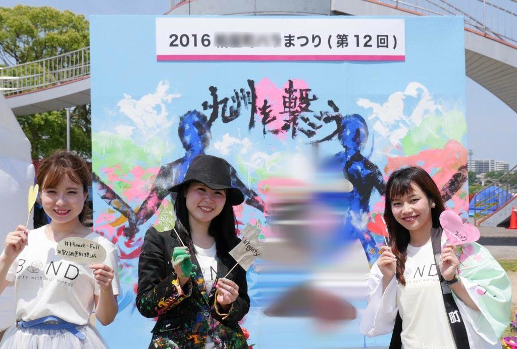 2016年粕屋町バラまつり看板の前でポーズをとる平野綾菜とミッシー