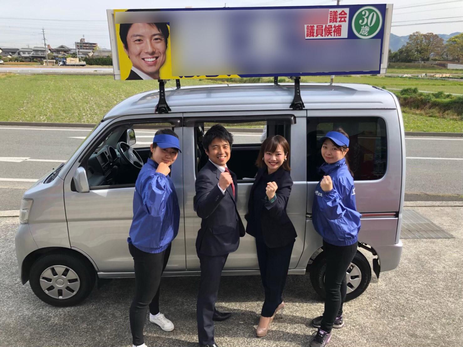 2019年地方議会議員選挙戦で選挙カーの前でガッツポーズする候補とウグイス