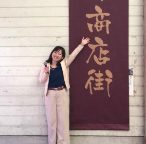 商店街の垂れ幕の横に立つ平野綾菜